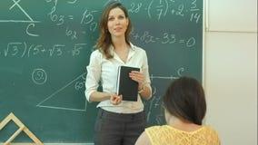 De bespreking van de glimlachleraar over wiskundige taak op groen bord in klaslokaal stock videobeelden