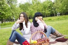 De bespreking van de moeder en van de dochter op de telefoon in het park Stock Afbeelding