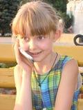 De besprekingen van het meisje door een mobiele telefoon Stock Foto's