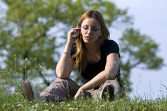 De besprekingen van het Meisje door een Mobiele Telefoon in Park. Royalty-vrije Stock Foto