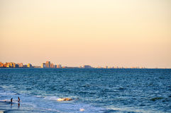 De besprekingen van het paar in golven op Strand kustlijn-1 van de Mirte Stock Afbeeldingen