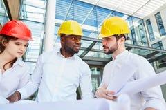 De besprekingen van de plaatsmanager aan architect en ingenieur stock afbeeldingen