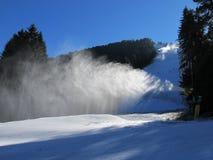 De bespuitende sneeuw van het sneeuwkanon op het spoor in het bos in de ochtend stock afbeelding