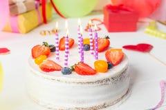 De bessencake van verjaardags gezonde yougurt met kaarsen op kleurrijke partijachtergrond met heldere partijhulpmiddelen, decorat Royalty-vrije Stock Fotografie
