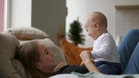De beste ogenblikken van het leven, koestert een houdende van gelukkige jonge moeder een pleegzoon, op een sneeuwwitte deken, op  stock video