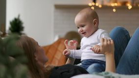 De beste ogenblikken van het leven, koestert een houdende van gelukkige jonge moeder een pleegzoon, op een sneeuwwitte deken, op  stock videobeelden