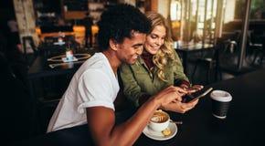 De beste vrienden bij koffie winkelen bekijkend slimme telefoon royalty-vrije stock afbeelding