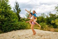 De beste vrienden hebben pret bij het strand piggyback royalty-vrije stock fotografie