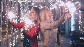 De beste vrienden met fonkelend vuurwerk vieren een vakantie in de nachtstad en hebben pret Langzame Motie stock video