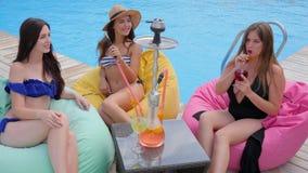 De beste vrienden in zwempakken die waterpijp roken en drinken cocktails dichtbij Zwembad stock footage