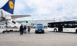 De bestelwagen van de politiedouane dichtbij Lufthansa-vliegtuigen in luchthaven stock afbeelding