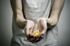 De bestrijding van drugs en drugsverslavingonderwerp: verslaafde die verdovende pillen op een donkere achtergrond houden royalty-vrije stock afbeeldingen