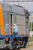 De bestuurder beklimt in de locomotief stock foto's