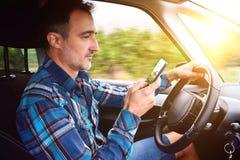 De bestuurder die een voertuig drijven die een telefoon gevaarlijk kant raadplegen wedijvert royalty-vrije stock fotografie