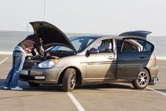 De bestuurder die van de auto de motor van de auto onderzoekt stock foto