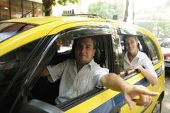 De bestuurder die van de taxi passagier een oriëntatiepunt toont Stock Foto's