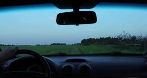 De bestuurder drijft de auto en de camera schiet het van binnenuit de auto stock footage