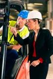De bestuurder en de supervisor van de vorkheftruck bij pakhuis Stock Foto's