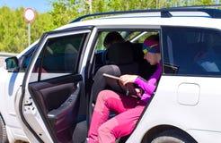 De bestuurder gaat zitten liftervrouw in auto Stock Afbeelding
