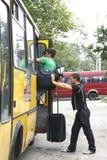 De bestuurder helpt passagiers met hun zakken Stock Afbeeldingen