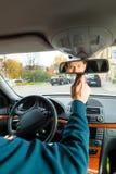 De bestuurder van de taxi kijkt in de drijfspiegel Stock Foto's