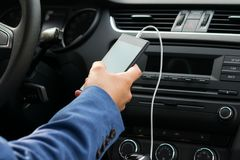 De bestuurder van het voertuig, houdt in zijn die hand de telefoon door een witte draad, aan het systeem van de auto'smuziek word stock foto's