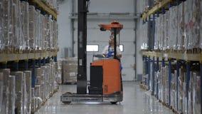De bestuurder van de pakhuisarbeider in de eenvormige dozen van het ladingskarton door van de laderfurnirure van de vorkheftrucks stock footage