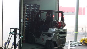 De bestuurder van vervoerbedrijf maakt pallets met goederen van vrachtwagen leeg stock video