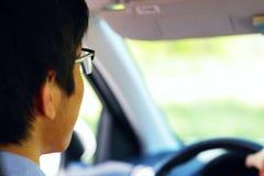 De bestuurder zit in zijn auto en drijft Royalty-vrije Stock Afbeelding