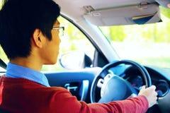 De bestuurder zit in zijn auto en drijft Royalty-vrije Stock Foto's