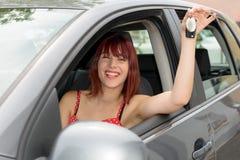 De bestuurdersvrouw die van de auto tonend nieuwe autosleutels en auto glimlachen Stock Foto