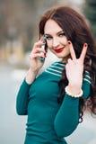 De betoverende vrouw in een heldere smaragdgroene kleding die op de telefoon, het glimlachen, het tonen spreken beduimelt omhoog  Stock Fotografie