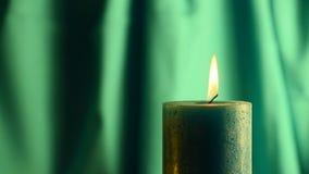 De bevende vlam van de wintertalingskaars met groene gordijnachtergrond stock footage