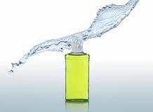 De bevochtigende shampoo bevindt zich op de blauwe achtergrond met plons Royalty-vrije Stock Afbeelding