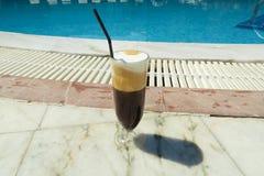 De bevroren cappuccino van koffiefreddo door de pool Stock Fotografie