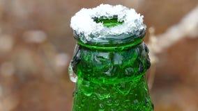 De bevroren hals van de bierfles bovenop ijs stock footage