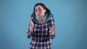 De bevroren jonge vrouw in sjaal en de glazen kunnen geen warme status op blauwe achtergrond krijgen stock videobeelden