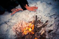 De bevroren mannelijke handen verwarmen over vuur bij de winternacht Stock Fotografie