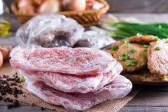 De bevroren varkensvleeshals hakt vlees en varkensvleesschnitzel in een plaat stock foto's