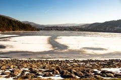 De bevroren vijver, stenen in de voorgrond is in de sneeuw, duidelijke blauwe hemel stock afbeelding