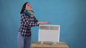 De bevroren vrouw in sjaal verwarmde daarna met een straalkachel op een blauwe achtergrond stock footage