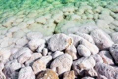 De bevuxna stenarna saltar vatten av det döda havet Arkivfoto
