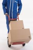 De bewegende pakketten van de leveringsmens met dolly Royalty-vrije Stock Afbeeldingen
