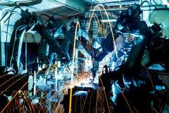 De beweging van de lassenrobot in een autofabriek stock afbeelding