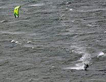 De bewegingen van een vliegersurfer over Lyall-Baai in Wellington New Zealand op een grijze stormachtige dag stock fotografie