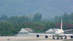De bewegingen van het Aiportpersoneel aan de auto dichtbij reus aiplane op vliegveld stock video