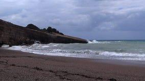 De bewolkte hemel, de wind en de golven breken op de rotsen op de kust stock videobeelden