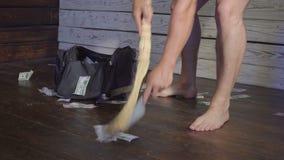 De bezem veegt dollars in huisvuillepel op de vloer Concept onverwachte rijkdom stock video