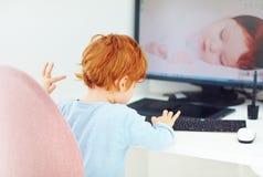 De bezige de babyjongen van de roodharigepeuter zit als bureauvoorzitter op werkende plaats en typt op toetsenbord Stock Fotografie