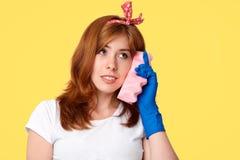 De bezige huisvrouw foolishes na het schoonmaken van alle ruimten, gebruiksspons als mobiele telefoon, beweert het spreken met vr stock foto